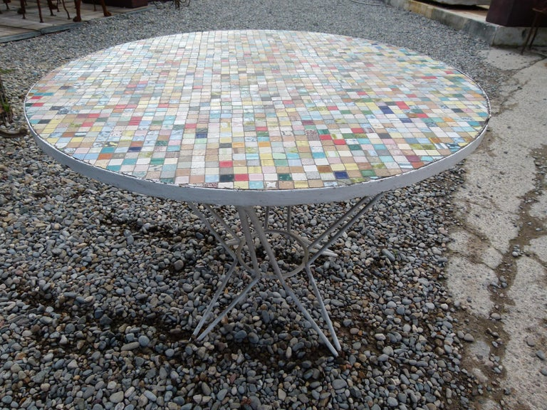 Multi-color round ceramic tile garden table with iron base painted in white. Ideal for terrace and garden. The multi colored tiles give a lively color to the place.