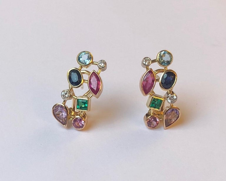 This stunning pair of earrings features several gemstones, such as topaz, emerald, diamond and amethyst. Each stone is set in white, yellow or rose 18kt gold, depending on the color as to best accentuate it.  This pendant was designed and made by
