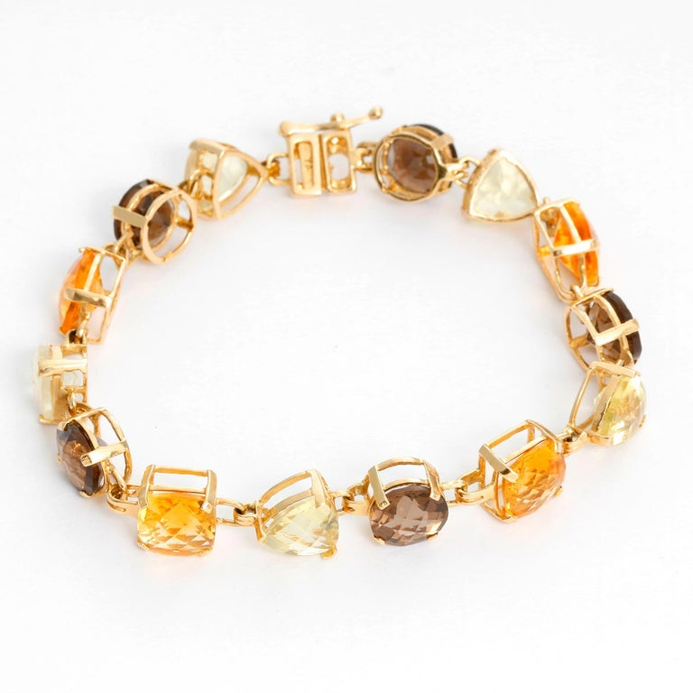 Multicolored Quartz and Citrine Set  - This bracelet and drop earrings with round- faceted smoky quartz, cushion -faceted Citrines and trianagle -faceted green quartz. Set in 14K Yellow gold. Will fit a 7 inch wrist. The earrings are 2 inches long.
