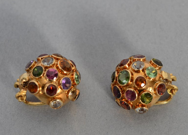 The domed, multigem Sputnik design is emblematic of the 1950's. These earrings are studded with faceted stones that include amethyst; peridot; citrine;  blue topaz and various shades of tourmaline. The stones are of varying sizes. Clip backs can be