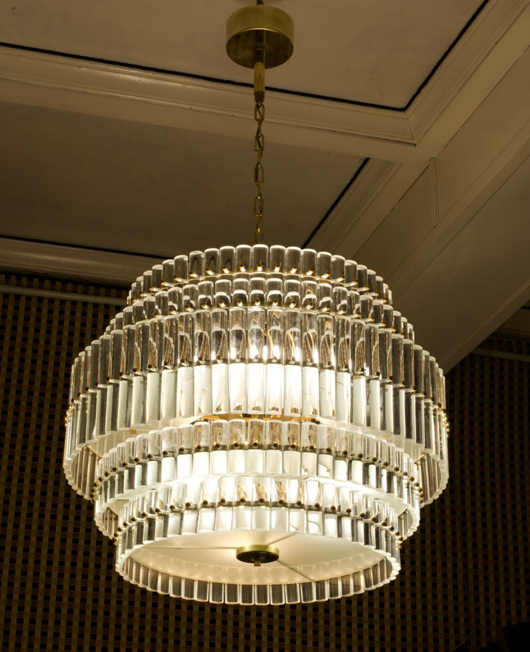 Fantastic round chandelier in Murano glass and polished brass, packed with small rods in half round of glass.  The chandelier is round in shape and consists of five floors of different diameters. The central one is the largest, then the two middle