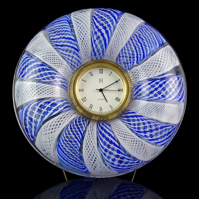 Beautiful Murano hand blown twisted blue and white Zanfirico ribbons Italian art glass desk clock. It has a Quartz clock face, a triangle stand on the back, and battery operated clock face (new battery, currently working). Has original Murano, made