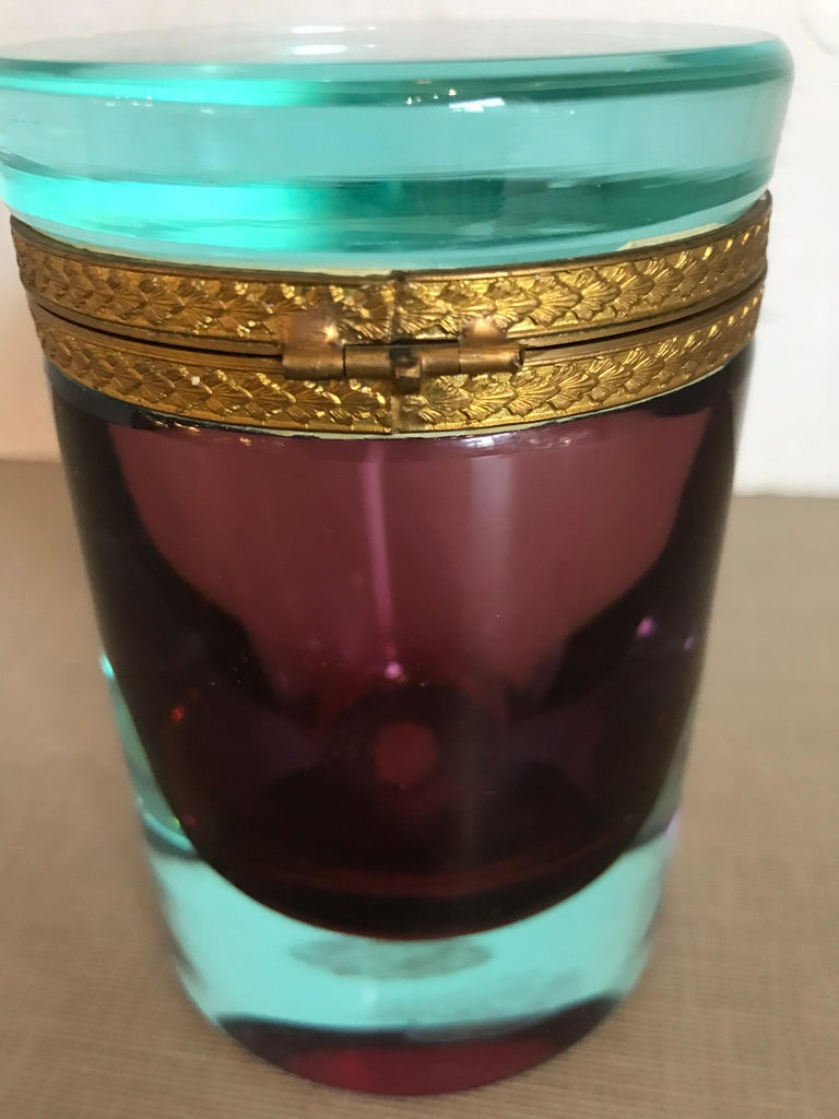 This is a heavy bi-colored turquoise and purple Murano glass cylinder box with brass ormolu rim probably from 1950s-1960s great condition.