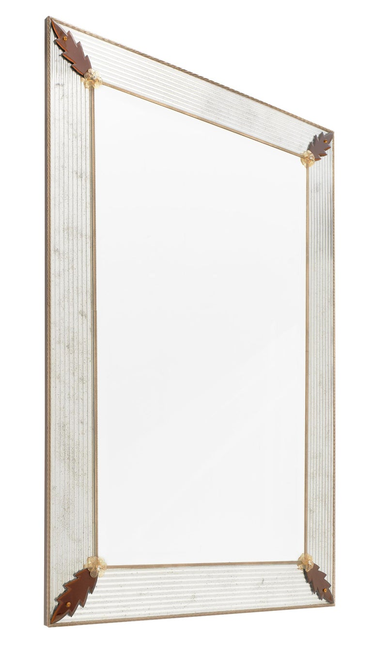 Murano glass amber leaf mirror by Giuliano Fuga. We love the beveled Murano glass which has been silvered and antiqued; framing the central mirror. The corners are adorned with amber leaf and flower details. It is a striking and impressive piece!