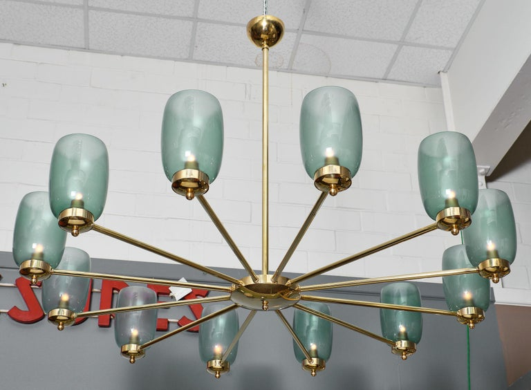 A stunning Murano glass and brass 12-arm chandelier featuring a solid brass structure. Each arm holds a large, light blue Murano glass bobeche. We loved the simplicity and strength of this piece. It has been newly wired to US standards.  Height