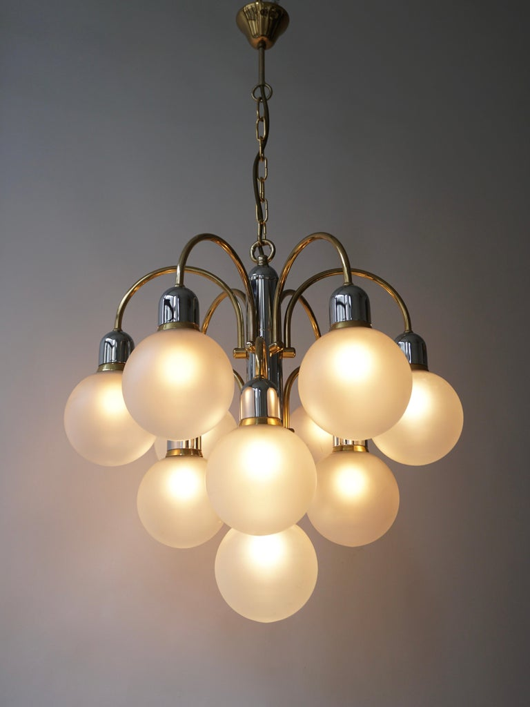A Italian chandelier in brass with ten arms of which each hold a Murano glass sphere. The bulbs are divided over three levels, creating an extravagant look.  The light created by this chandelier is very pleasant and ambient.  Measures: Diameter