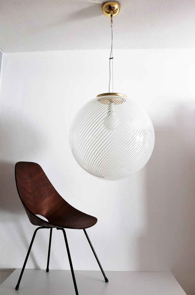 Beautiful and very big glass globe pendant lamp with shiny white stripes and brass details.