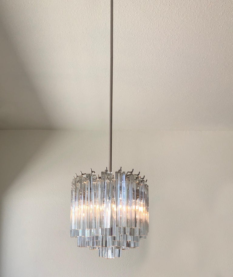 """A glamorous 1970s clear Murano glass and stainless steel oval chandelier by Venini. The chandelier has been newly rewired, It takes six candelabra lightbulbs. Overall height with rod is 50 inches, it can be shortened if desired. Dimensions: 13"""""""