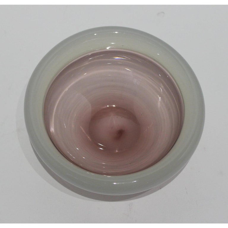 This stylish Murano glass bowl dates to the 1980s and was created by Seguso. The base of the bowl in a translucent violet color with a band of Opaline glass.