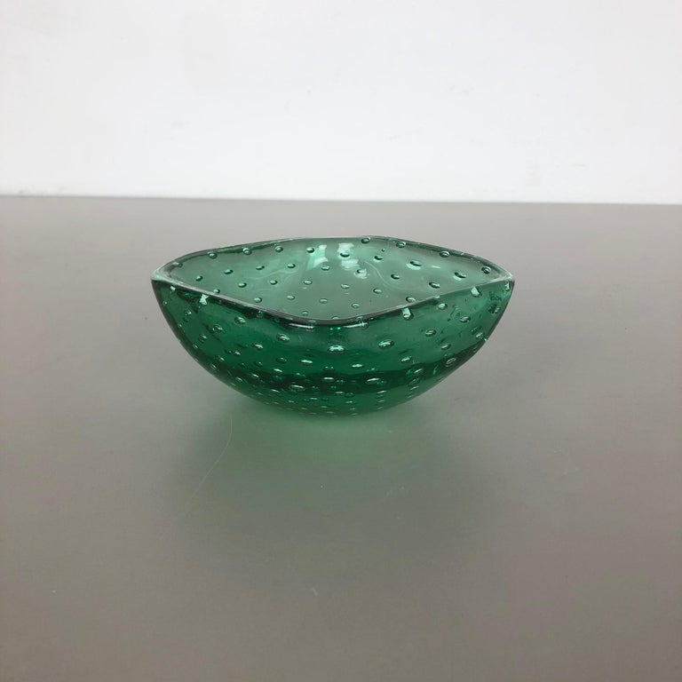 Article:  Murano glass bowl, ashtray element   Origin:  Murano, Italy   Decade:  1970s   This original glass shell bowl was produced in the 1970s in Murano, Italy. An elegant green Murano glass element utilizing the bullicante