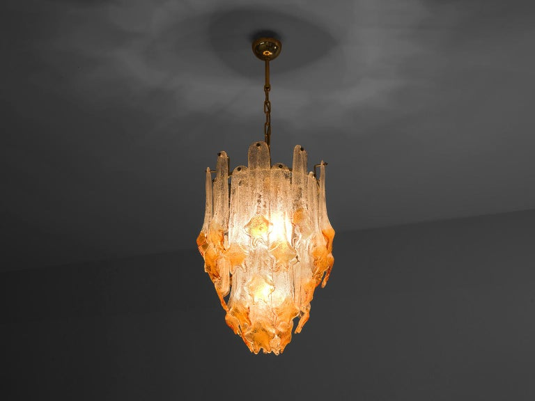 Mazzega, chandelier, Murano glass, brass, Italy, 1970s  This chandelier by Italian manufacturer Mazzega consists out of multiple long glass leaves that hang on four levels. Each transparent leaf ends in a floral form that is highlighted with orange
