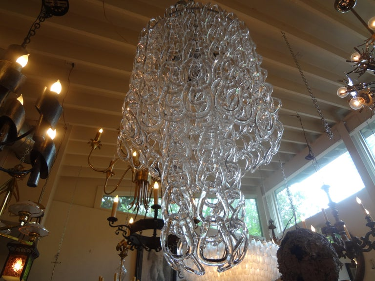 Interesting large Murano chandelier or Murano glass lantern inspired by Mangiarotti of Murano, Italy. This stunning Mid-Century Modern Murano glass chandelier has blown glass chain pendants creating a lovely effect. Our offered Hollywood Regency
