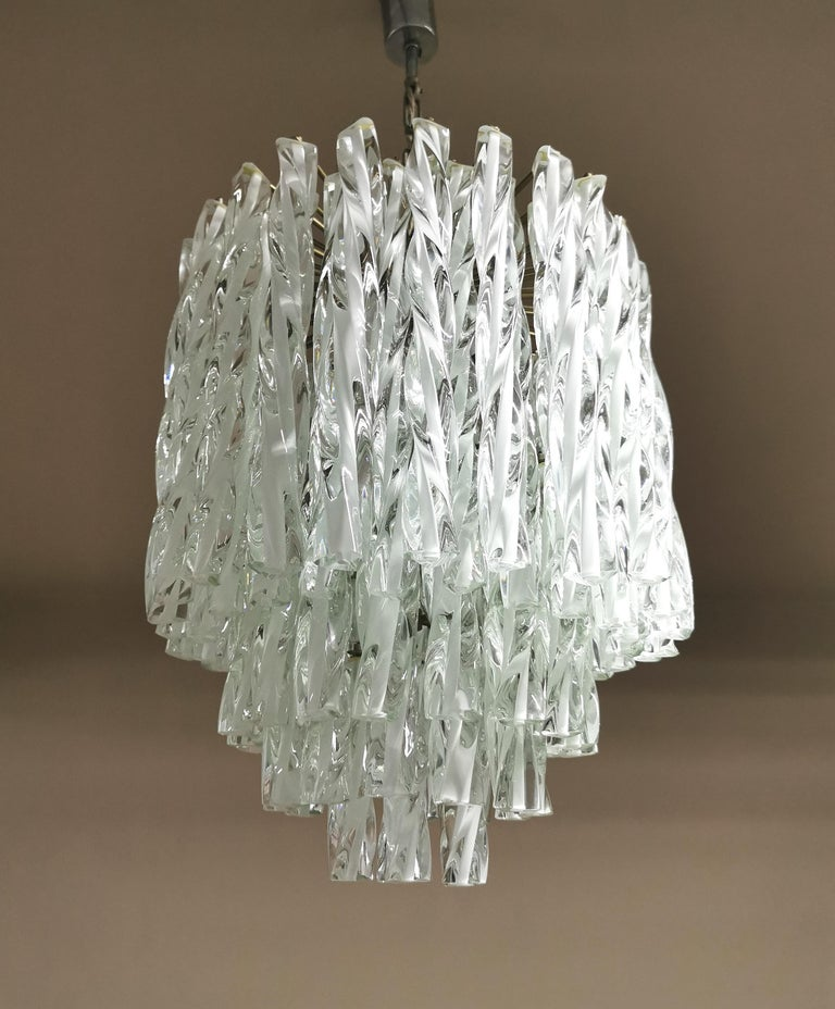 Rare and elegant pair of Venini chandeliers with transparent blown Murano trihedron glass pendants with white inside. The peculiarity of this pair are the non-linear but braided glass pendants that give a wonderful and unique play of light. The