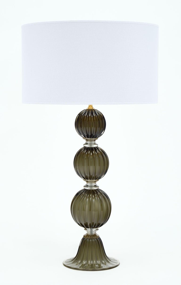 """Pair of Italian Murano glass dark smoke lamps featuring stacked spheres with glass rings fused with 23-carat """"avventurina"""" gold. This pair is by Alberto Dona. They are newly wired to fit US standards. The white shades have beautiful gold interiors."""