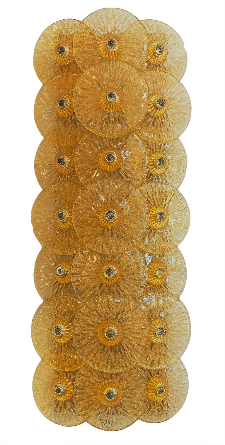 Beautiful Murano glass disc sconces by Carlo Nason. This Italian pair of important fixtures feature 21 light amber hand blown glass discs, each textured and arranged vertically on a polished brass structure. They have been newly wired to fit US