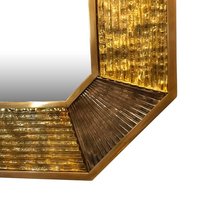 Contemporary Italian ribbed gold Murano glass framed mirror with darker Murano glass decorative accented corners. Thin bronze frame surround the Murano glass border.