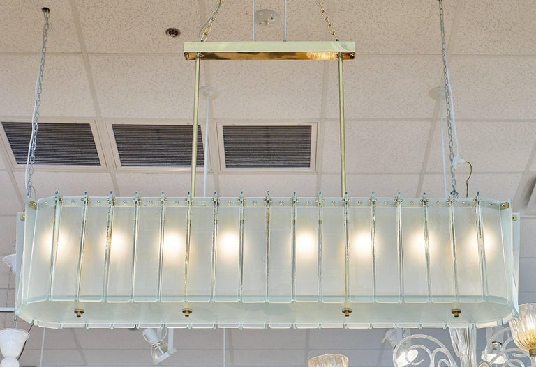 Superb modernist Murano glass frosted chandelier featuring light blue frosted blades tied with gilt brass nuts to an oblong brass structure. This piece has been newly wired to fit US standards.  This chandelier is currently located at our dealer's