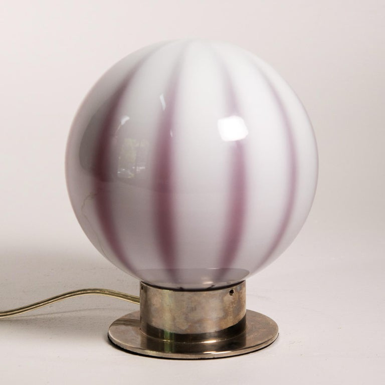 Murano glass globe shaped table lamp the cased glass shade with red/purple tones with white panels fitting into a silver plate base. When the lamp is off, it is more purple, when on shines red. Made in Italy by Global Views.