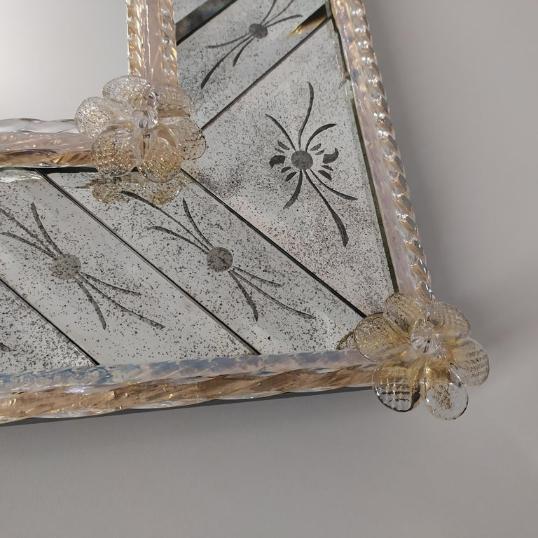 Rectangular Murano glass mirror in Venetian-style, made by the expert hands of the Masters of Murano, with a frame composed of beveled and hand-engraved pieces on an antiqued mirror, with finishing of crystal reeds on a golden background and gold