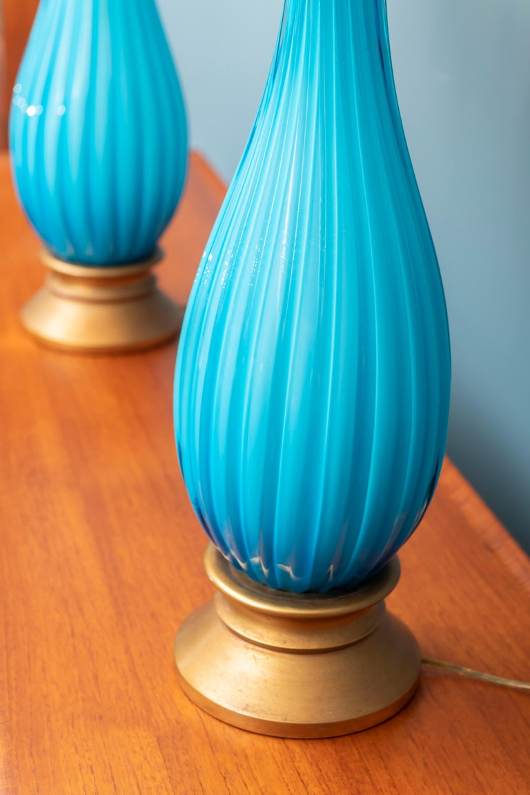 Murano glass table lamps by Mabro, Los Angeles CA. Stunning aqua blue color with brass and gilt metal mounts, shades are by association and in good condition.