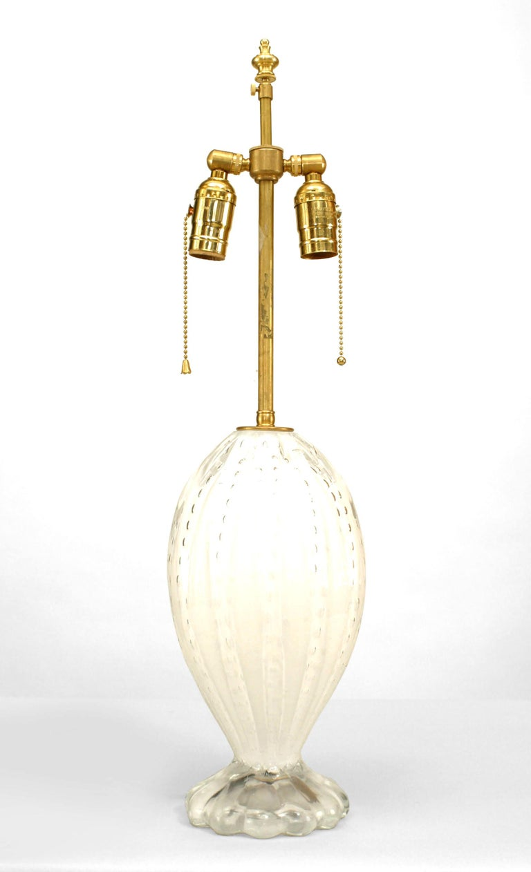 Two table lamps composed of translucent white murano glass in an oval form with a scalloped base and internal bubble design (modern). Each is fitted with a centered brass rod which supports two downward-facing bulbs.  2 - PRICED EACH (one slightly