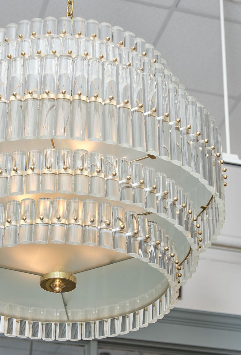 Murano glass tiered rod chandelier from the island of Murano in Italy. This piece features a gilt brass structure supporting five rows of clear glass rods hand blown by artisans in Murano. We love the glamorous way the light filters through the