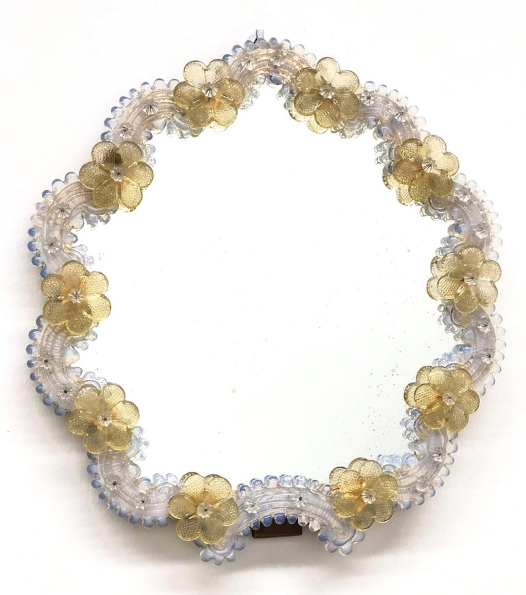 A gorgeous Murano glass vanity mirror surrounded with handmade light yellow flowers. Can be used as a table or a wall mirror. With minor signs of wear as expected with age and use. A nice addition to any girls or ladies room. Mirror with smaller