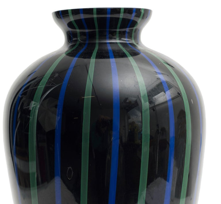 Beautiful Murano glass vase. The vase is black decorated with green and blue vertical lines. Created in 1970s. Very good conditions.