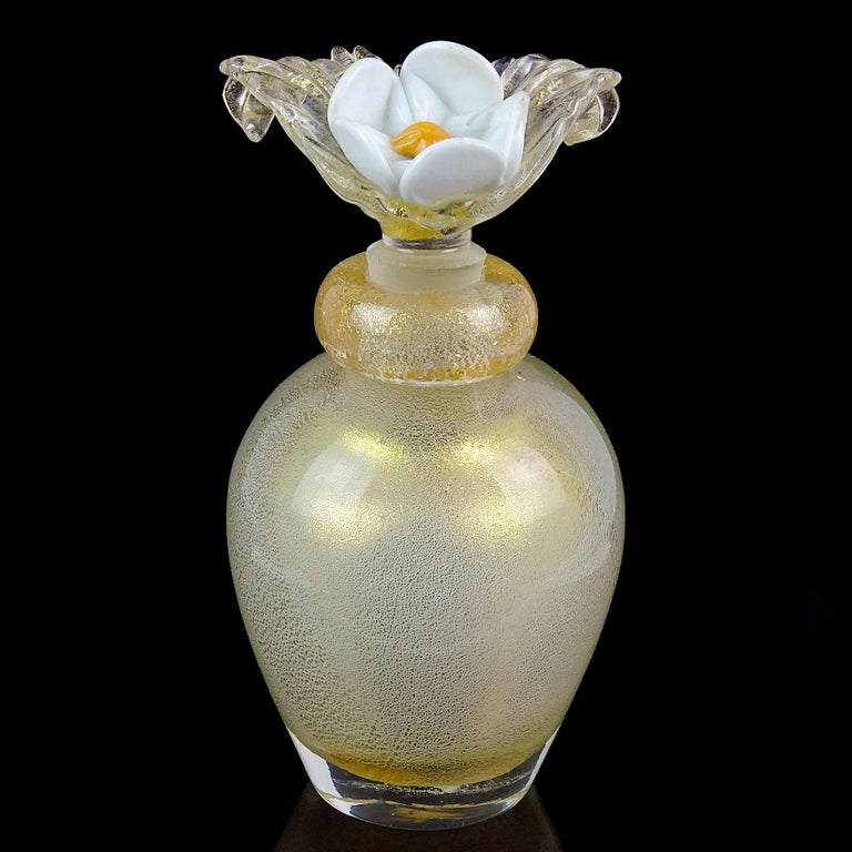 Gorgeous vintage Murano hand blown gold flecks over white Italian art glass perfume bottle. Attributed to designer Archimede Seguso. The bottle has a beautiful large flower stopper, in white with bright orange center and clear leafs with gold. The