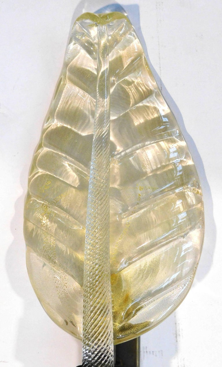 Italian leaf shaped wall light shown in hand blown Murano glass infused with 24-karat gold flecks mounted on natural brass frame / Made in Italy 1 light / E14 or E12 / max 40W Depth: 5 inches / Width: 9 inches / Height: 21.25 inches 5 in stock in