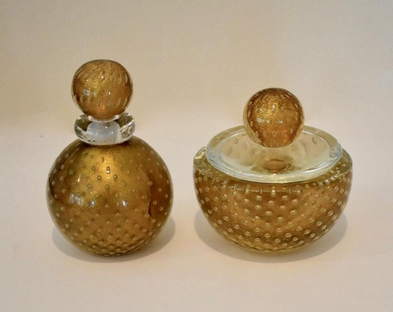 2-piece Murano glass set consisting of a stoppered bottle or jar and lidded bowl by Seguso, Murano, Italy. Thick cased clear glass surrounds a bronze colored interior with delicate gold inclusions control bubbles in between the two layers. Archimede