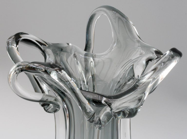 A stunning Italian Murano grey cased sculptural art glass vase dating from 1950-1970. This heavily made hand blown vase is made in clear glass with an encased grey glass centre the slender body with four wing like applications with extend to the top