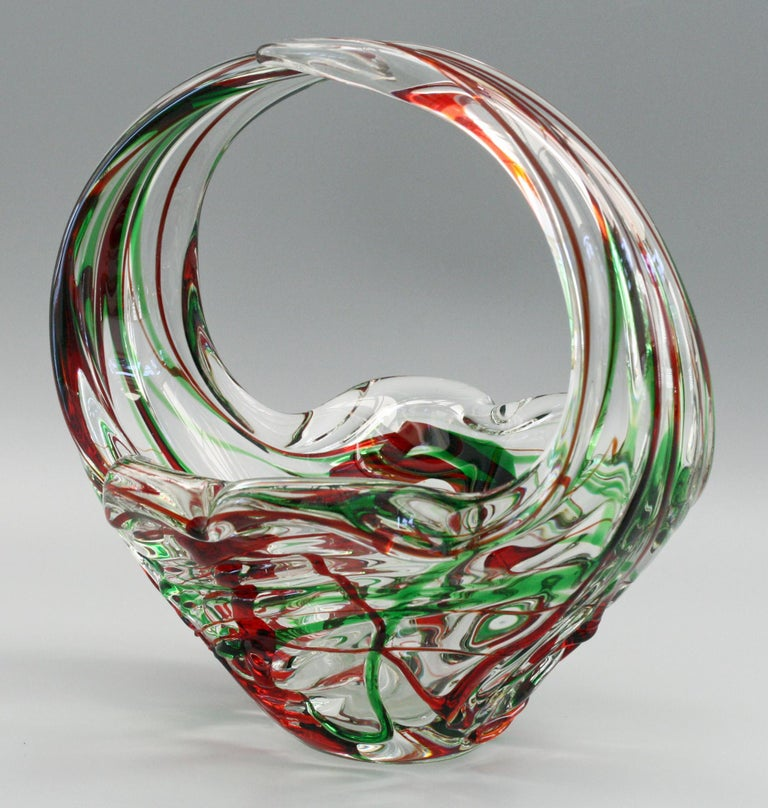 A very striking and stylish Italian Murano art glass basket shaped bowl with red and green trailing dating from the mid-20th century. The bowl is heavily moulded in clear glass has a flower shaped base with two raised overlapping loop handles. The