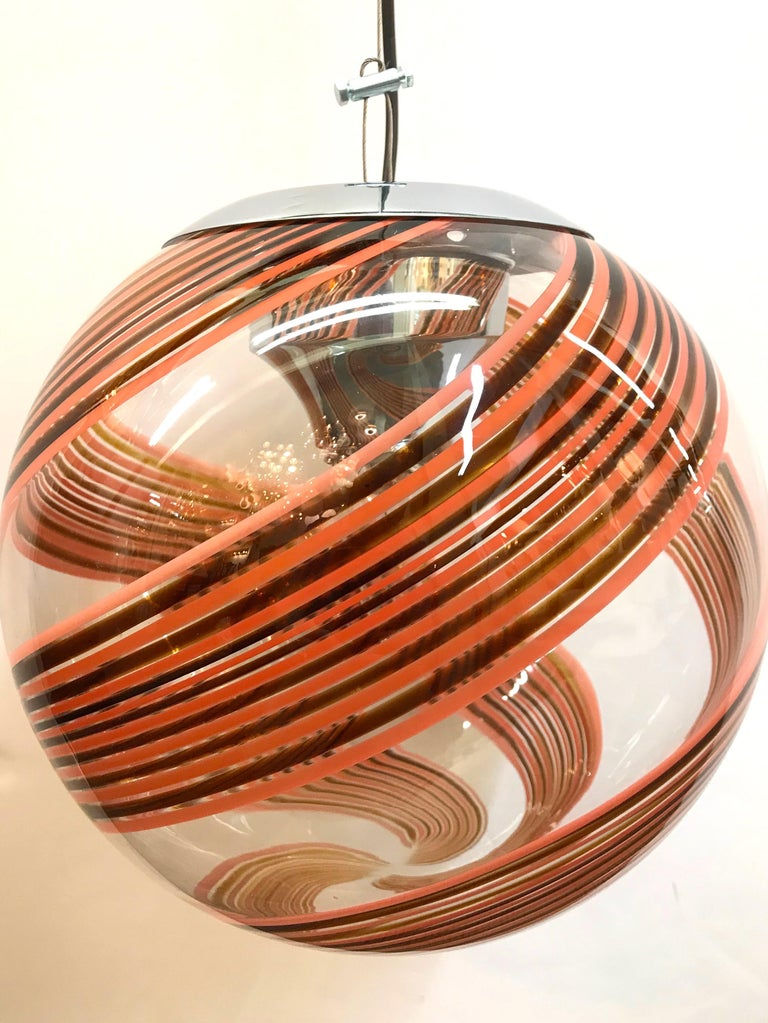 A beautifully handblown clear glass globe with chocolate brown and blush stripe swirl shade pendant light, circa 1970. Original stylized chrome mount and dome ceiling canopy. The pendant is suspended on steel cord with the black electrical next to