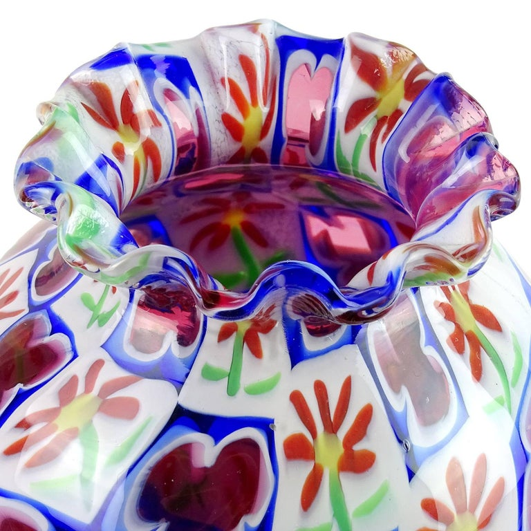 Beautiful vintage Murano hand blown Millefiori daisy and clover Italian art glass cabinet / bud vase. Documented to the Fratelli Toso Company. It has a crimped rim, with unusual shape. The mosaic design has white, orange, green, purple / pink and