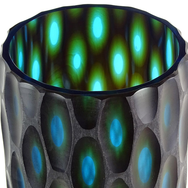 Large modern Murano hand blown black over blue green layers Italian art glass sculptural flower vase with carved surface. The piece has carved ovals throughout, showing the blue and green layers. Measures: 13 1/4