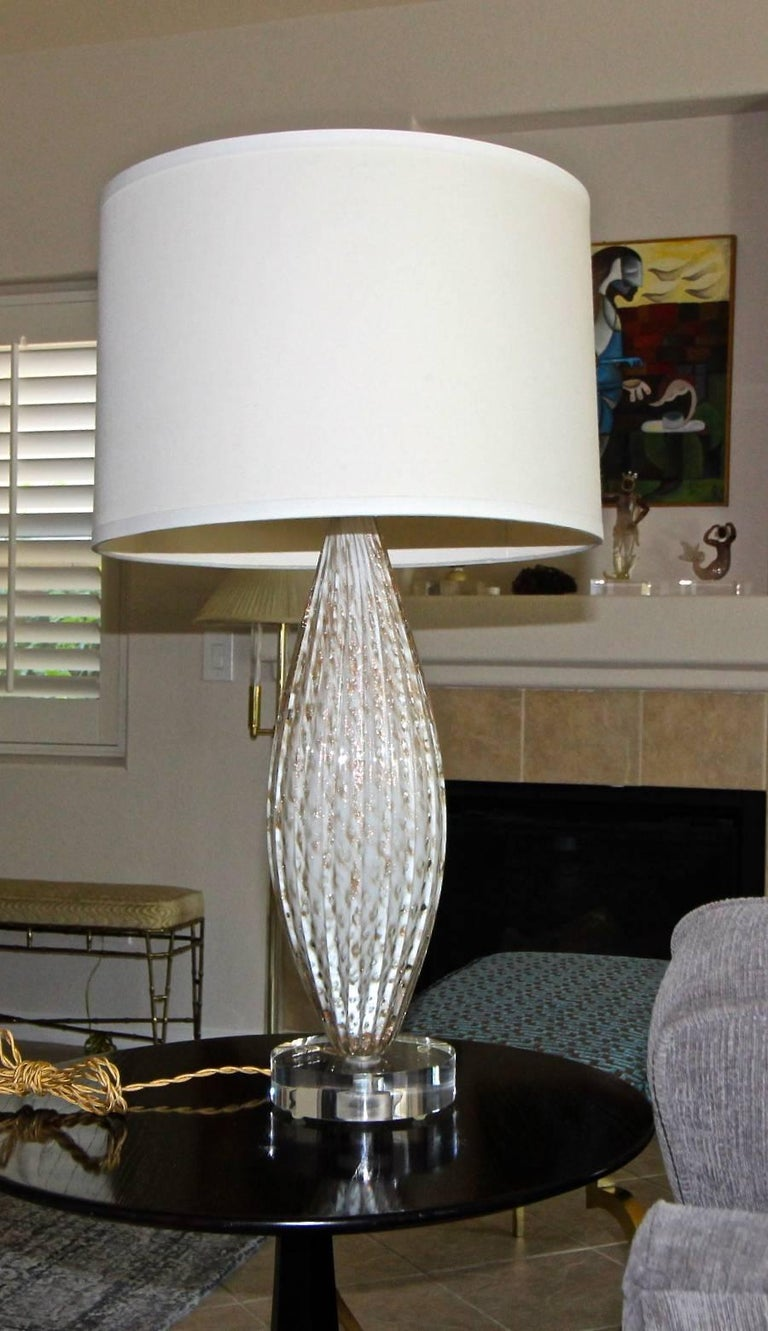 Murano oval shaped white colored glass table lamp with aventurine inclusions. Newly wired for US on custom acrylic base with brass fittings, full range dimmer socket and French style twisted rayon covered cord.  Measures: 19.5