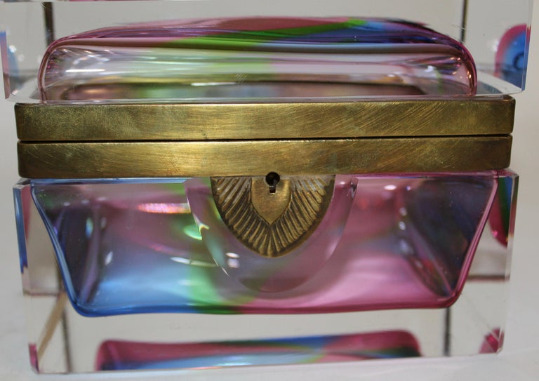 An Italian 1960s Murano glass polychromatic glass box. The thick glass with an eye-catching display of colors ranging from pinks, blues and greens creating a rainbow effect, encased in a layer of clear glass. Finished with a gilt mount and keyhole,