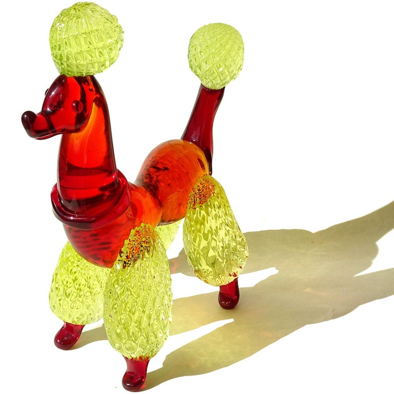 Beautiful large Murano hand blown red and yellow Italian art glass poodle puppy dog sculpture. It has a quilted pom-pom design on the legs, tails and puff on its head. Red collar on his neck. The fur glows under a black light, from the Uranium