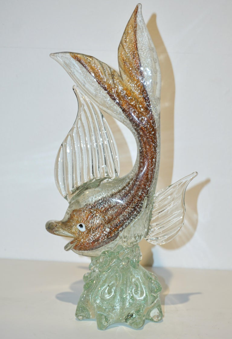 Italian midcentury sculptural Murano glass fish. Realized using the Sommerso technique, a clear layer of glass blown over the amber color glass, worked in bullicante, the air bubbles trapped inside the glass (technique made famous by Archimede