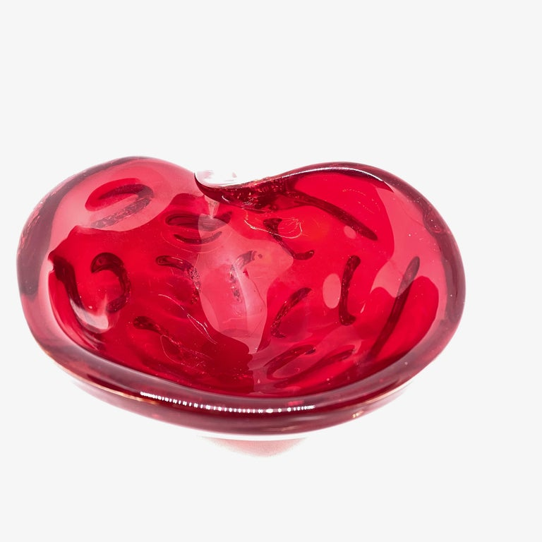 Gorgeous hand blown Murano art glass piece with Sommerso and bullicante techniques. A beautiful organic conch sea shell shaped bowl, catchall or ashtray in deep red, Italy, 1980s.