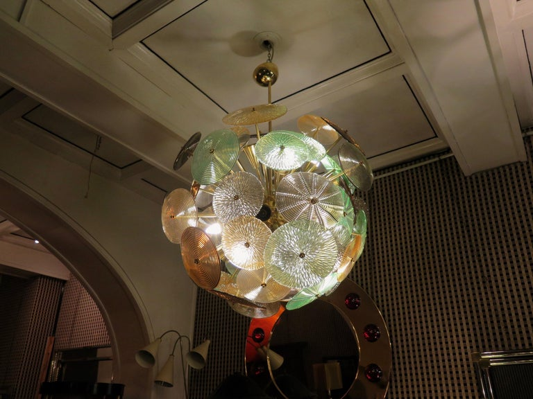 The large glass multicolored disks make up this Murano chandelier from the 1960. A Classic Sputnik from the middle of the century.  Made of a large central sphere in which brass rods are screwed, glass disks are placed above the brass rods. Of