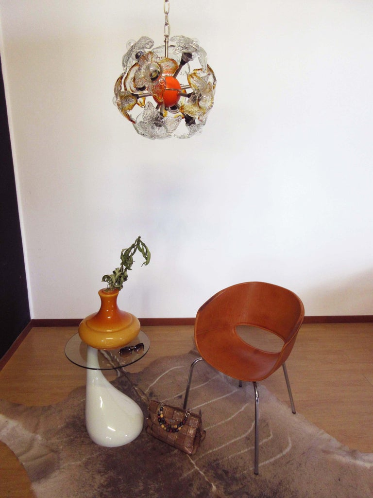 The Sputnik lamp from Mazzega has twelve fixtures surrounding a orange central sphere element. The fixtures are surrounded by Murano glass elements shaped like flowers, 6 trasparent glasses, 6 trasparent and amber glasses Period: 1970s Dimensions: