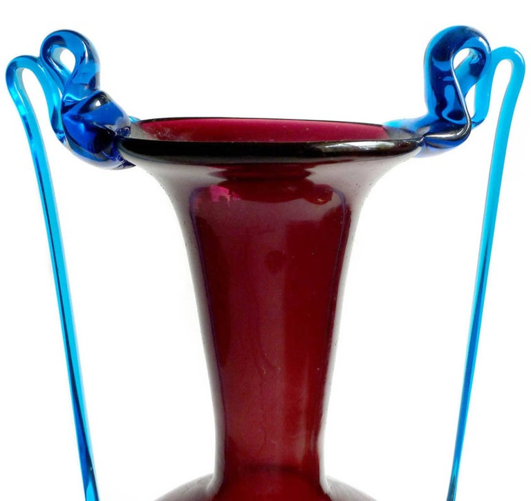 Gorgeous and delicate antique Murano hand blown burgundy red and cobalt blue Italian art glass double handle vase. Attributed to the Fratelli Toso Company, circa 1930s or earlier. Created in the Venetian style. The piece has very thin applied long