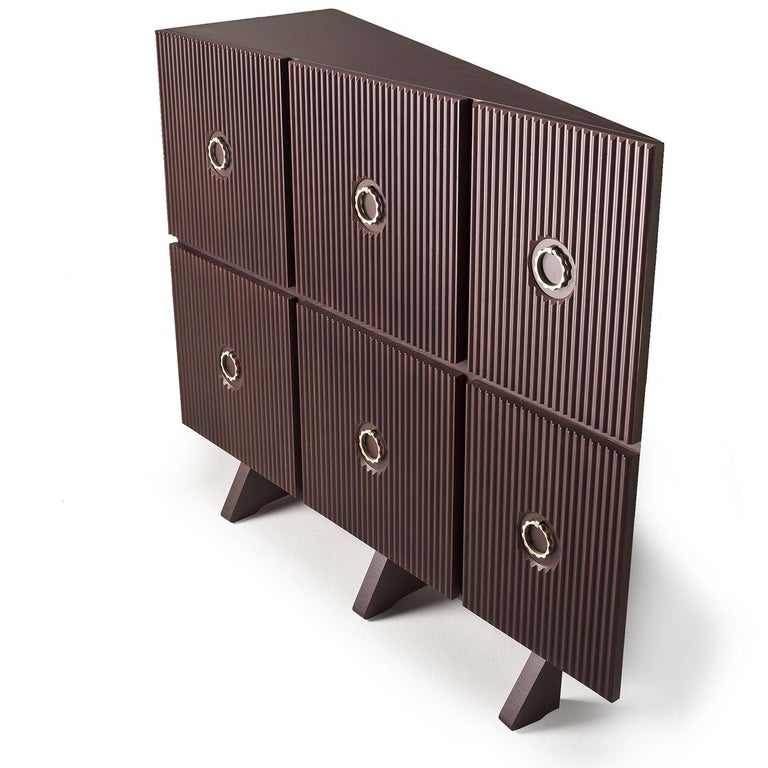 An unconventional piece that will make a statement in an eclectic or contemporary interior, this cabinet is a stunning example of modern design crafted with traditional methods. Its wooden structure rests on a plinth base and comprises a combination