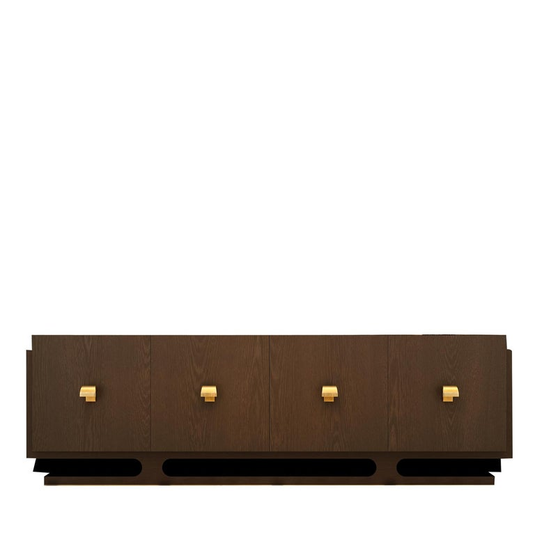 Deeply inspired by Mid-Century Modern furniture design, this wooden sideboard strikes with its glossy finish, enhancing the wood's vertical grain. Equipped with hook-like handles with a brass finish, the four front panels open to reveal spacious