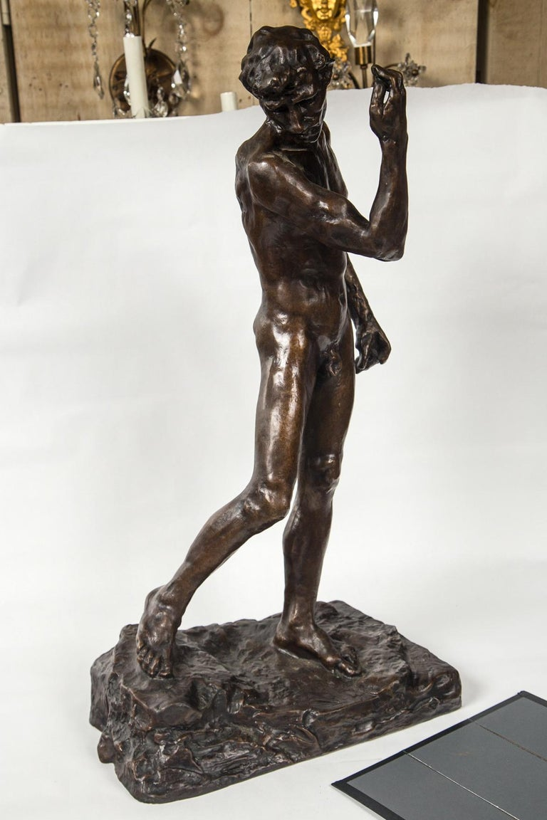Dark patinated bronze in a striding position.
