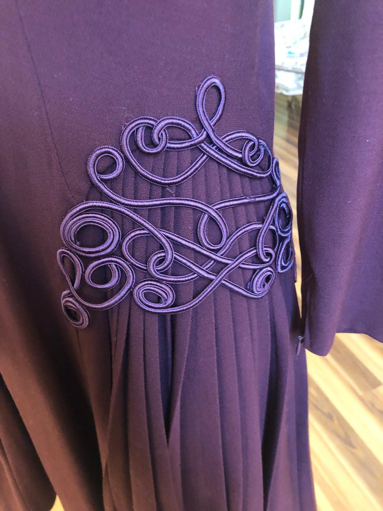 This is an incredible 1940s  Jacques Fath Dress (Jacques Fath passed away in 1954) in excellent condition. Some of the details are decorative braiding; soft pleats; longer side hems; darting, and zips at cuffs.  The color is aubergine, and there is