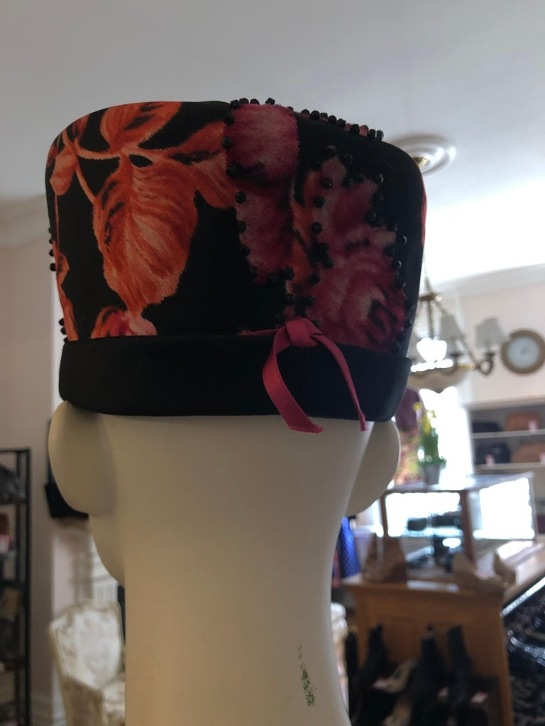 This rare 1950s Schiapearelli hat is made of satin with a textured floral pattern and bugle/jet beads. It has lining which allows the hat to keep its form and a stiff satin border/band. The museum wothy hat is in unworn condition.  The circumference