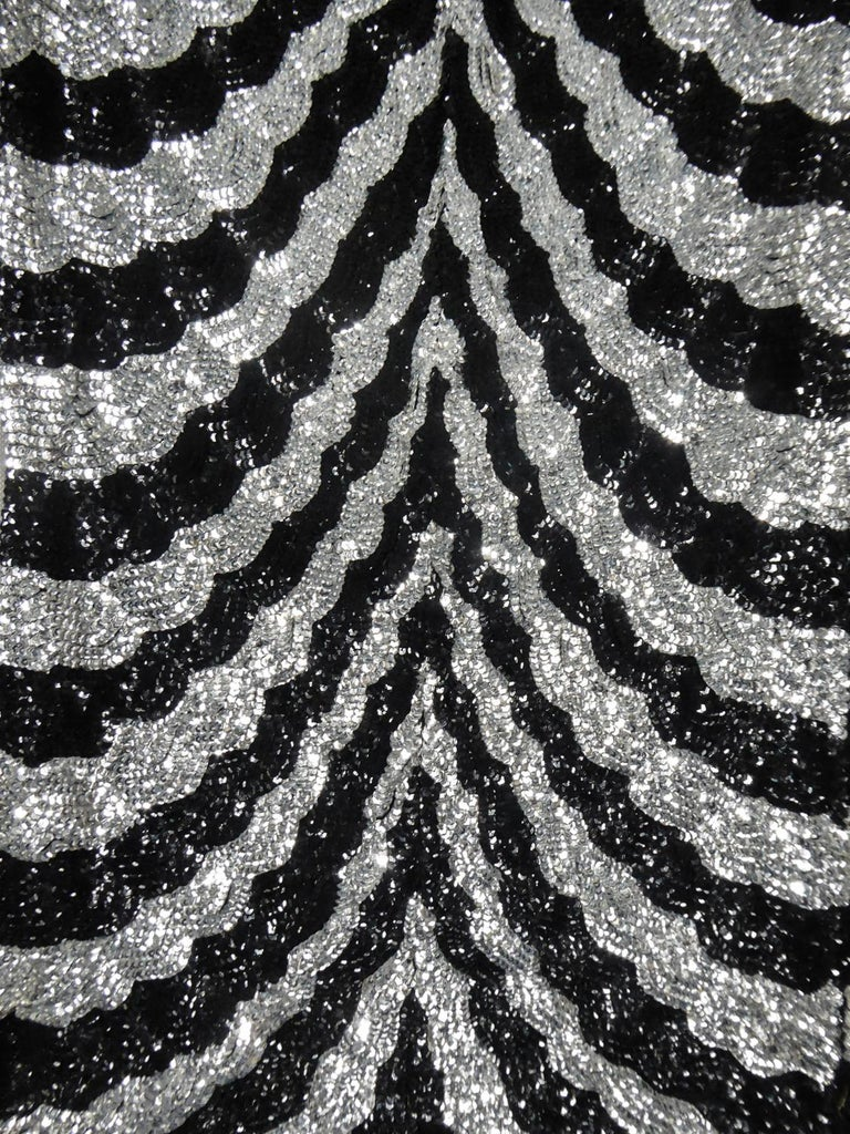 Circa 1980/1985 France  Music-Hall Evening Dress inspired by Art Deco in Silver and embroidered with black and silver faceted paillons and silver tubular pearls from the 1980s. Skin-tight dress with short flounced sleeves with small shouder pads.